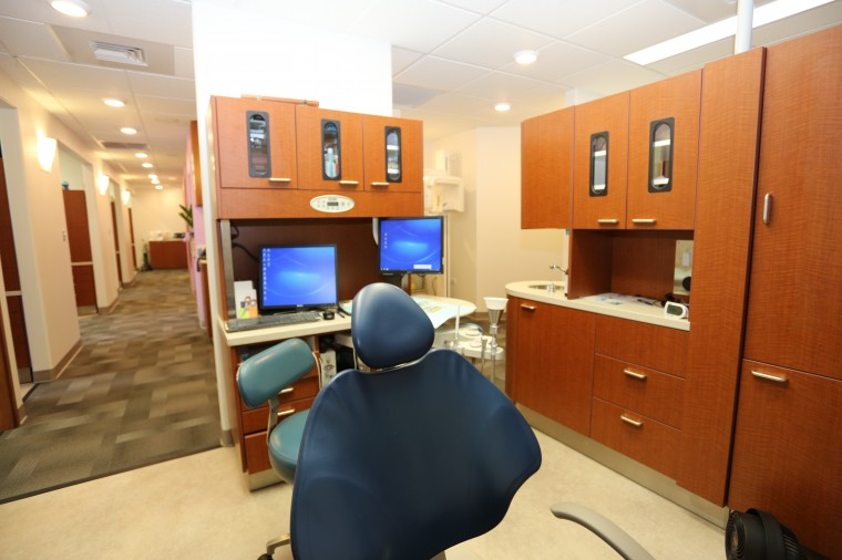 photo of our new office aiea pearl city dental care built in 2013 photo of hallway and a dental room with chair and two computer screens and new cabinetry